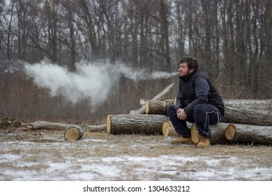 adorable young adult male is sitting on the woodwith forest trees in the background blowing cloud of vapor from ecigarette