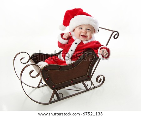 8f8ed1aa0273 Adorable young baby wearing a santa claus suit and hat sitting in a metal  Christmas snow sleigh - Image