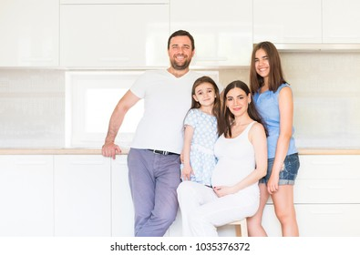Adorable young big family embracing on kitchen. Happiness and love concept