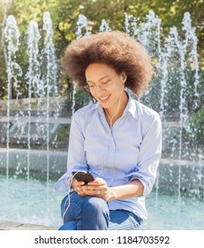 Adorable Young Black Woman With Glasses Using Smartphone. Outdoor Portrait, Casual Wear , Looking At The Phone