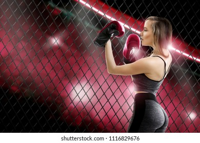 Adorable young blomde girl mma fighter with beautiful round buttocks in red gloves inside the cage