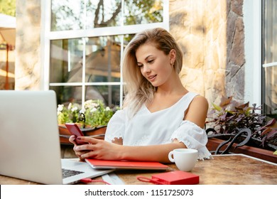 Adorable young blonde businesswoman reading sms on her cell phone, while working with laptop, woman sitting with cup of coffee at the cafe. Outdoors.