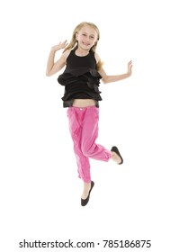 Adorable young blonde caucasian girl wearing pink pants and a black top with frills. The girl is jumping and smiling.