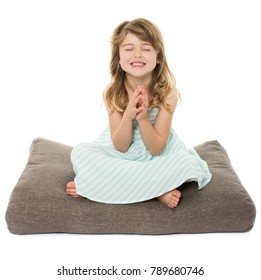 Adorable young blonde caucasian girl wearing a blue and white striped dress. The girl is isolated and smiling. She is sitting on a grey pillow.
