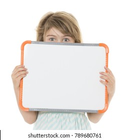 Adorable young blonde caucasian girl wearing a blue and white striped dress. The girl is isolated and smiling. The kid is holding a white board.