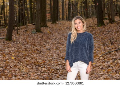 Adorable young blonde woman in blue sweater and jeans stands in autumn woods