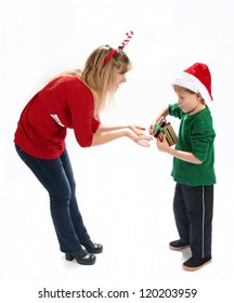 Adorable young boy giving gift to mother for Christmas