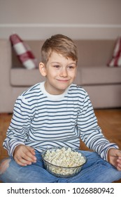 Adorable young boy with popcorn in bowl sitting on the floor in living room