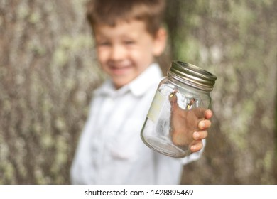 Adorable young boy smiling and holding a jar with fireflies or lightning bugs in it.