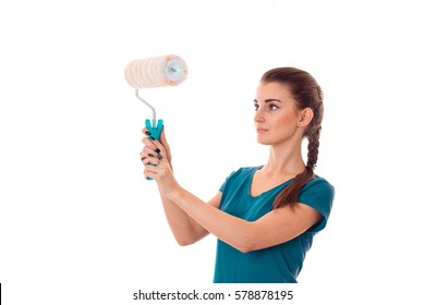 adorable young brunette builder girl in uniform makes renovation with paint roller in her hands isolated on white background