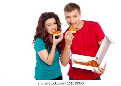 Adorable young couple relishing yummy pizza. Indoor studio shot
