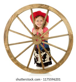 An adorable young cowgirl smiling from behind a large western wheel. Isolated on white.