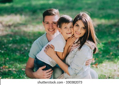 Adorable young family having weekend in a city park