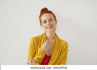Adorable young female with ginger hair, freckles and shining eyes full of happiness, wearing yellow and red clothes, smiling gently into camera being glad to meet her friends or recieve message