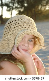 Adorable Young Girl at the Beach in Straw Hat