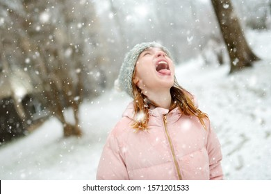 Adorable young girl catching snowflakes with her tongue in beautiful winter park. Cute child playing in a snow. Winter activities for kids.