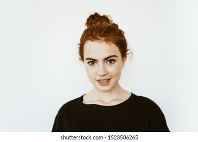 Adorable young girl with curly red hair braided in a bun on her head, with freckles on her face on a white background in a dark jacket cute smiles