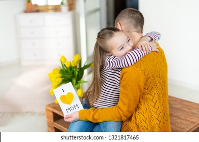 Adorable young girl giving her mom, young cancer patient, homemade I LOVE MOM greeting card. Family celebration concept. Happy Mother's Day or Birthday Background.