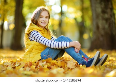 Adorable young girl having fun on beautiful autumn day. Happy child playing in autumn park. Kid gathering yellow fall foliage. Autumn activities for children.