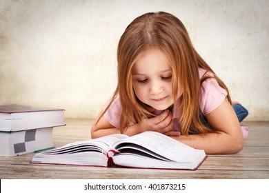 Adorable young girl reading a book