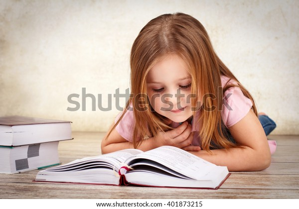 Adorable young girl reading a book