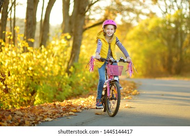 Adorable young girl riding a bike in a city park on sunny autumn day. Active family leisure with kids. Child wearing safety helmet while riding a bicycle.