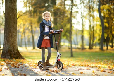 Adorable young girl riding her scooter in a city park on sunny autumn evening. Pretty preteen child riding a roller. Active leisure and outdoor sport for kids.