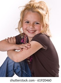 Adorable young girl smiling for the camera in a brown shirt and jeans on a white background