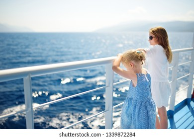 Adorable young girls enjoying ferry ride staring at the deep blue sea. Children having fun on summer family vacation in Greece. Kid sailing on a boat.
