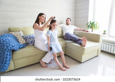 Adorable young pregnant family in living room. Mother combing her daughter's hair. Happiness and love concept