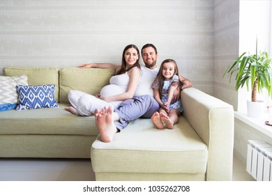 Adorable young pregnant family in living room. Happiness and love concept