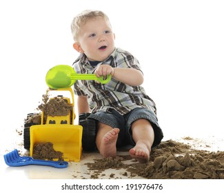 An adorable, young preschooler happily looking up as he dumps sand onto his toy bulldozer.  On a white background.