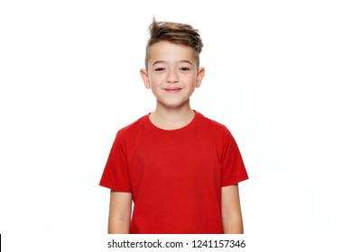 Adorable young teenage boy waist up studio portrait isolated over white background. Handsome boy looking at camera with cheeky smile.