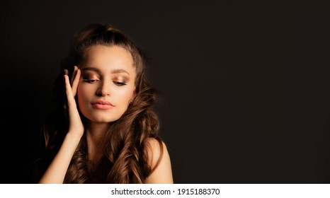 Adorable young woman with perfect skin and professional makeup posing at black background. Empty space