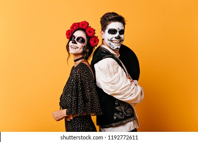 Adorable zombie girl in rose wreath posing on yellow background. Happy couple with muerte makeup having fun in halloween.