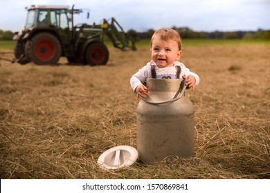 An adorably Bavarian baby boy standing in a milk churn laughing happily. In the background a tractor is turning  the hay the milk churn in standing on.