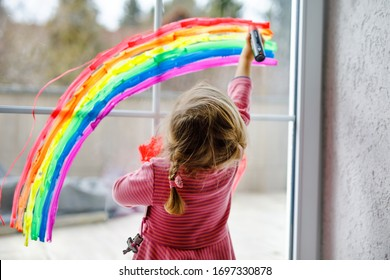 Adoralbe little toddler girl with rainbow painted with colorful window color during pandemic coronavirus quarantine. Child painting rainbows around the world with the words Let's all be well.