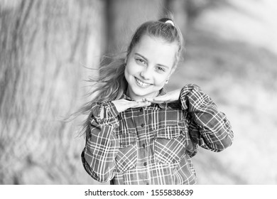 Adorbale baby face. Happy kid with cute face look. Small girl smiling with healthy young face skin and long blond hair outdoor. Little child with cute smile on her face on summer landscape.