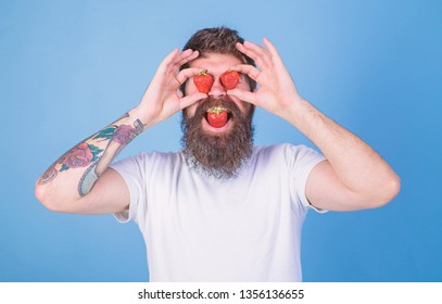 Adore strawberry. Man in love with strawberry. Man bearded happy love adore enjoy juicy red ripe strawberry. Hipster with beard adores strawberry hold berries as eyeglasses. Berries sweet happiness.