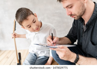 Adoult man writes notes of simple melody on music sheet for his younger brother, who learn to play guitar