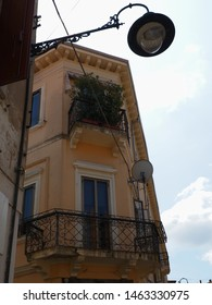 Adria, Italy. Elegant building, detail, windows and balcony. There is an old street lamp.