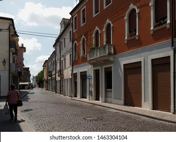 Adria, Italy. Historic center, a lady walks in the shade, it is noon on a sunny day.