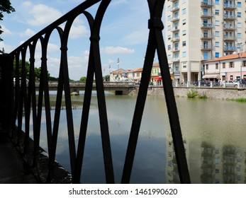 Adria, Italy - July 13, 2019. The Canal Bianco, waterway, and bridge. In the foreground the railing along the river.