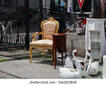 Adria, Italy - July 13, 2019. Flea market in the historic center. Chair, cabinets, fake swans.
