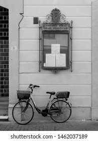 Adria, Italy - July 13, 2019. Historic centre. Railway timetables showcase. There is a bicycle. Black and white photo.