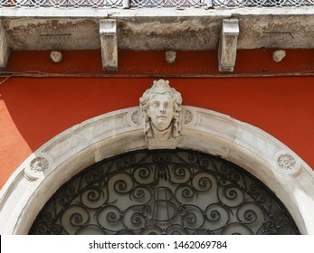 Adria, Italy - July 13, 2019. Historic centre. Ancient red palace in venetian style. Entrance, detail. Sculpture above the door, a woman's head.