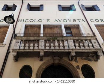 Adria, Italy - July 13, 2019. Historic center, facade of an ancient palace. Entrance, balcony, lamppost, windows.