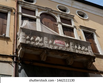 Adria, Italy - July 13, 2019. Historic center, facade of an ancient palace. Balcony with anti-pigeon net and for rent sign.
