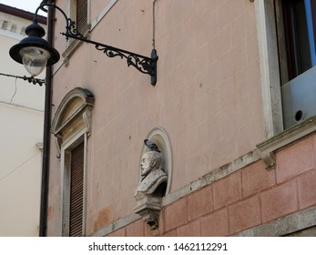 Adria, Italy - July 13, 2019. Historic center, facade of an ancient palace. Sculpture, head with a pigeon on it. Old lamppost.
