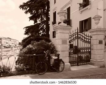 Adria, Italy - June 13, 2019. Ponte Castello, bridge. Old villa and bike. Sepia photo.